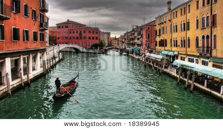 Gondola passing by venetian canal among multicolored houses in Venice.