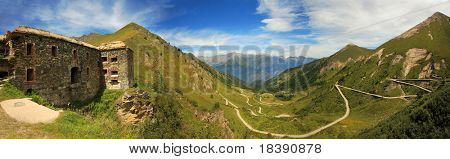 Panoramic view on ancient fortifacation and unpaved road through the valley in Alps, Italy.