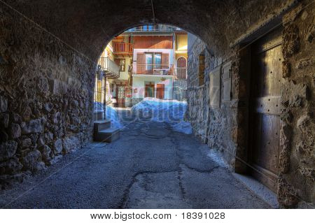 Old stoned arch and house front yard in Limone Piemonte, northern Italy.