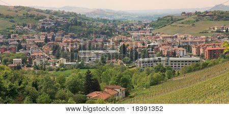 Vista aérea panorámica sobre la ciudad de Alba entre colinas en Piamonte, norte de Italia.