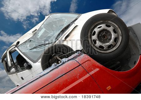 car crash with a red and white car and a blue cloudy sky