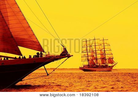 nostalgic sailboats sailing the ocean at sunset or sunrise