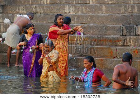 hindu men and women bathing in the ganges river in varanasi