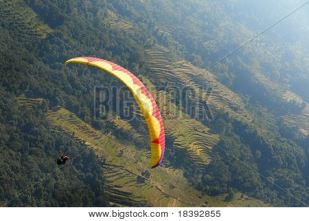 paragliding in nepal above green rice terraces (photo taken during paraglide)