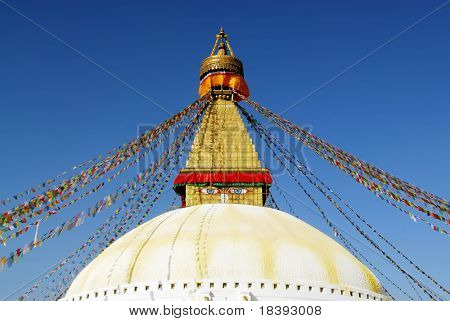 bodhnath stupa with buddha eyes and prayer flags with clear blue sky