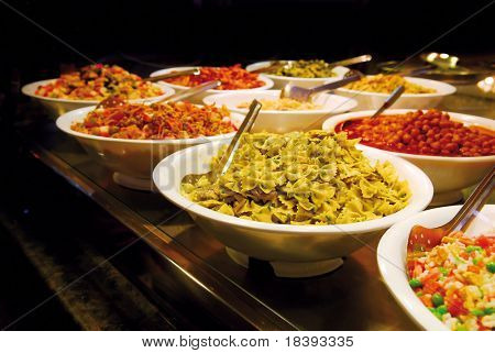 Buffet with butterfly shaped pasta, vegetables, meat, seafood salads on Boqueria market in Barcelona