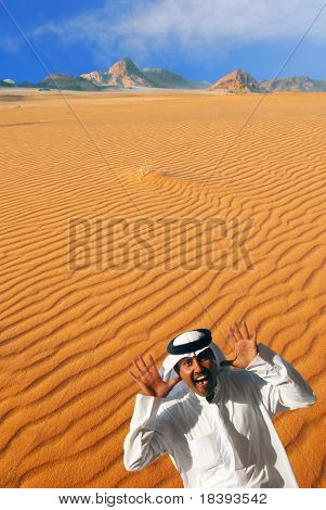 Traditional arabian man laughing, making funny face and playing peek-a-boo  in Wadi Rum desert, Jordan