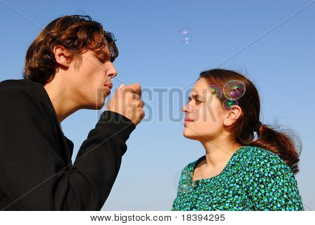 Concept: stay young! Man in his twenties blowing soap bubbles to his girlfriend