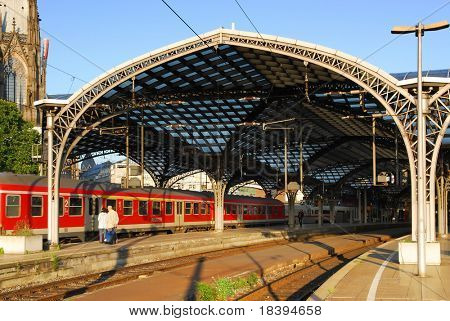 Red train arriving at railway station in Cologne, Germany