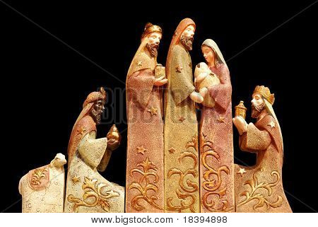 Religious christmas group with 3 kings, joseph, mary, baby jesus and a sheep on black background