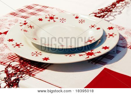 Off-white and red table setting with plates and napkins for christmas