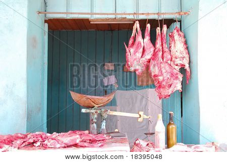 Colorful butcher shop with vintage scale and red meat in colonial town Baracoa, Cuba