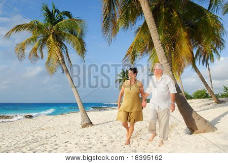Active senior couple walking on the beach, enjoying retirement on tropical destination: Maria la Gorda on caribbean island Cuba