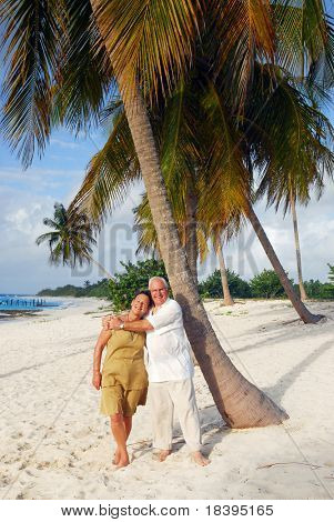 Romantic senior couple on the beach embracing each-other, enjoying retirement on tropical destination: Maria la Gorda on caribbean island Cuba