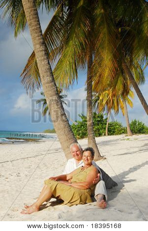 Happy senior couple sitting on the beach embracing each-other, enjoying retirement on tropical destination: Maria la Gorda on caribbean island Cuba