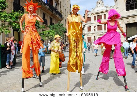 HAVANA - CIRCA DEC 2008 : Colorful Cuban girls dance on stilts and entertain tourists circa December 2008 in Havana. This salsa group is a daily tourist attraction in Havana.