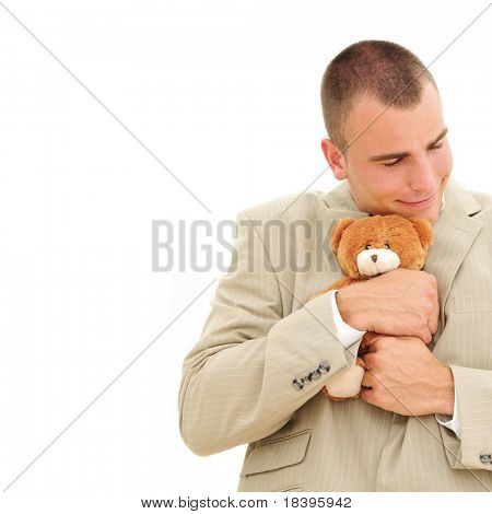 Businessman showing his soft site while cuddling a teddybear, isolated on white background