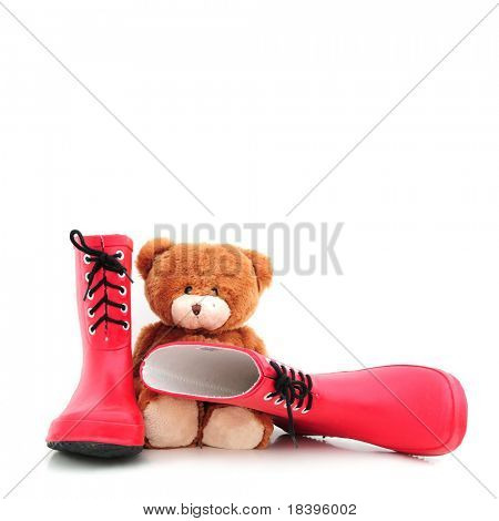 Red rubber boots for children with teddybear as christmas present, isolated on white square background