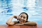 stock photo of swimming pool family  - asian woman making a phone call at swimming pool - JPG