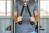 Fitness man exercising triceps muscles in the gym with pull-down ropes fitness equipment machine att poster