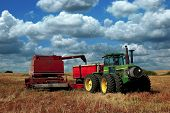 stock photo of truck farm  - A pull combine dumps a load of Canola into a grain truck at harvest time - JPG