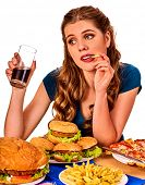 Woman eating french fries and hamburger. Student consume fast food on table. Girl drinks cola and dr poster