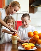 stock photo of orange-juice  - Happy mother with children squeezed orange juice - JPG