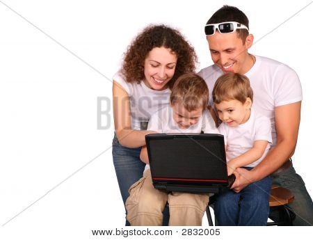 Family Of Four With Notebook