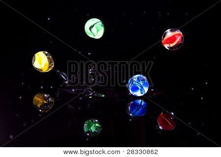 Marbles Bouncing Off Dark Surface