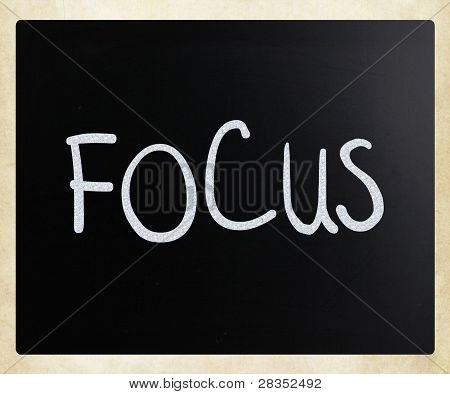 "The Word ""focus"" Handwritten With White Chalk On A Blackboard"