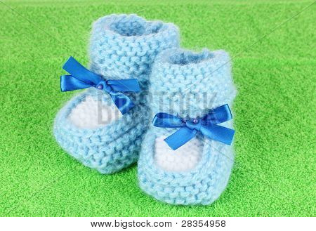Blue baby booties on green background