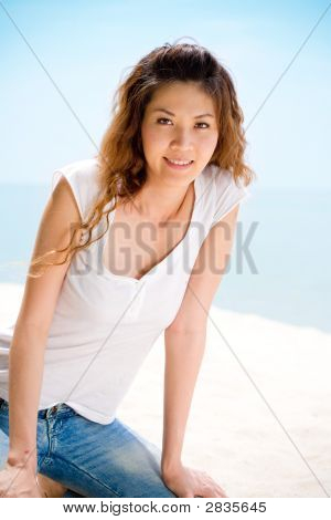 Happy Woman Sitting At The Beach Happily