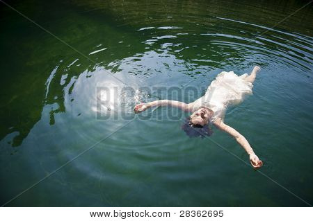 Beautiful young woman on white dress floating in lake, relaxing body and mind.
