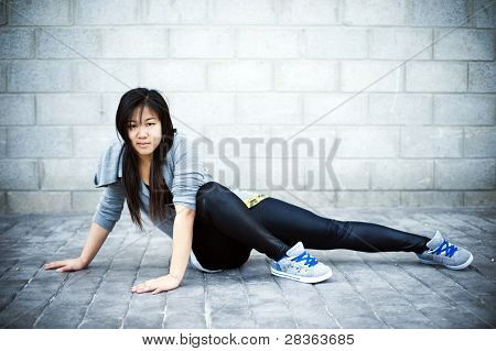 Menina asiática sentando-se no contexto urbano.