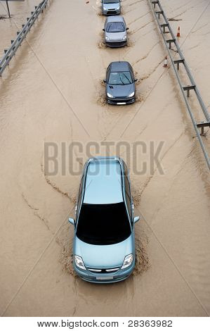Cars going throught flood highway