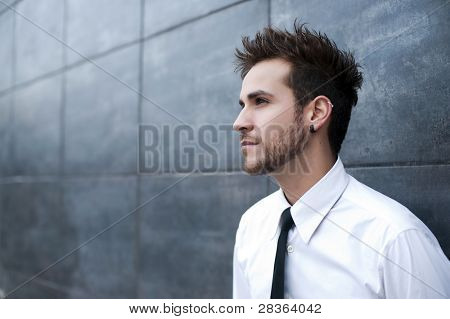 Young handsome man looking thoughtful (piercing in ear)