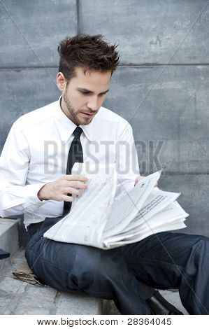 Young handsome man reading newspaper