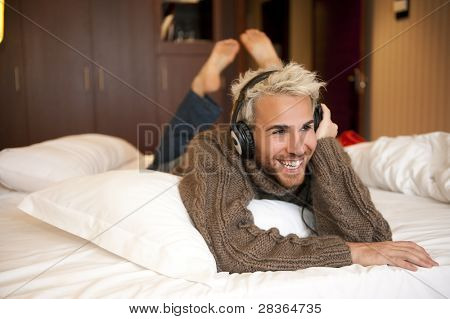 Man listening music with headphones at home.