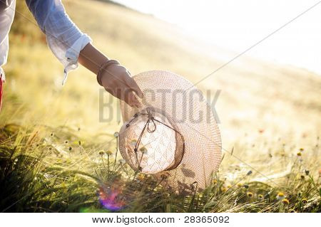 Woman hand holding a hat in sunny day