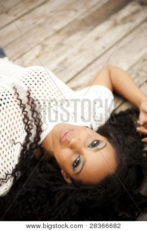 Young thoughtful woman lying on wooden pier