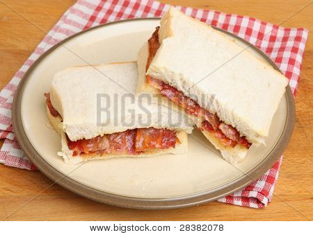 Crispy streaky bacon between thick white bread slices