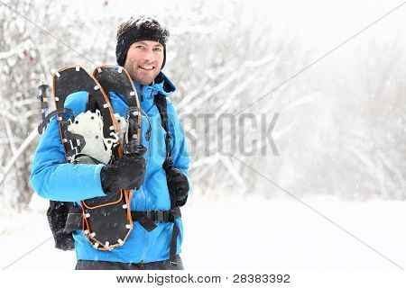 Winter snowshoeing. Young outdoorsman hiker standing smiling happy holding snowshoes outside in the snow during snowshoe hiking trip. From Quebec, Canada.