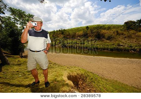 A tourist is standing in green nature. The man is a senior and is holding a camera. Dominican Republic.