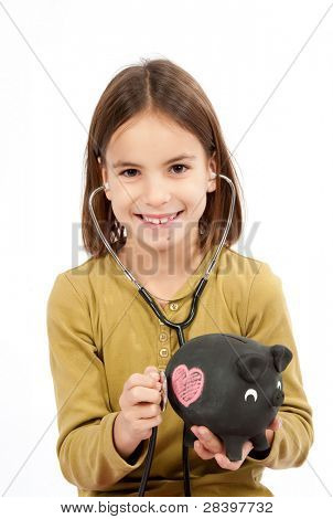 little girl with stethoscope and piggy bank on white background