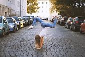 Carefree Young Woman Doing Spontaneous Handstand In The Middle Of City Street poster