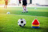Soccer Ball And Cone Marker On Green Artificial Turf With Blurry Of Soccer Player Training poster