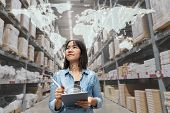 Portrait Of Happy Young Attractive Asian Entrepreneur Woman Looking At Inventory In Warehouse Using  poster