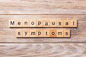 Menopausal Symptoms Word Written On Wood Block. Menopausal Symptoms Text On Wooden Table For Your De poster