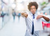Afro american man holding blank paper contract over isolated background pointing with finger to the  poster