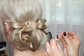 picture of bobbies  - Stylist hands making hairdo with a hairpin - JPG
